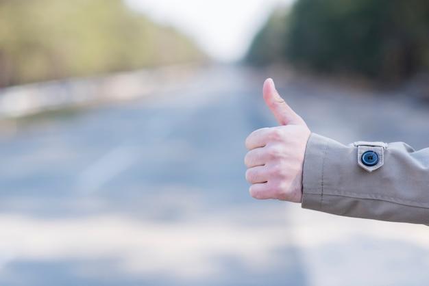 田舎道でヒッチハイク男の手のクローズアップ