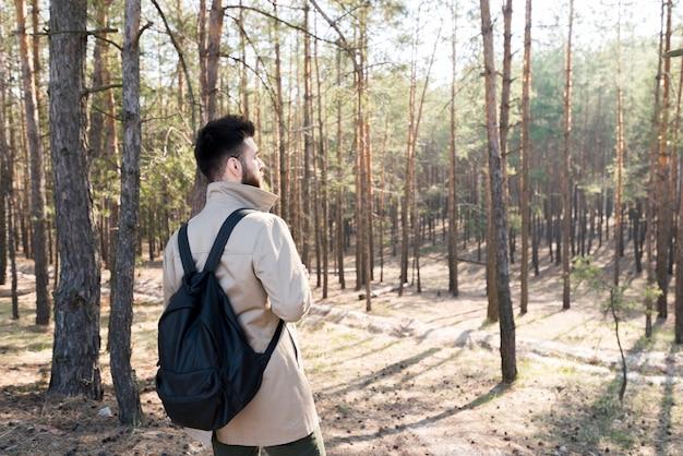 森の中に立っている彼のバックパックを持つ男の背面図