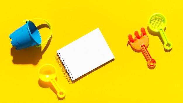 夏のサンドボックスオブジェクトと明るい面上のメモ帳