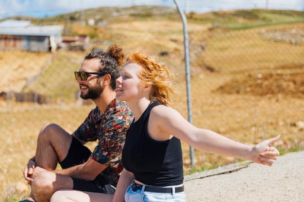 若いカップルが道端でヒッチハイク