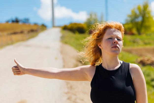 道端でヒッチハイクの若い女性