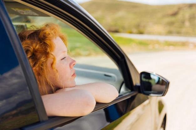 車の窓の外を見て若い女性