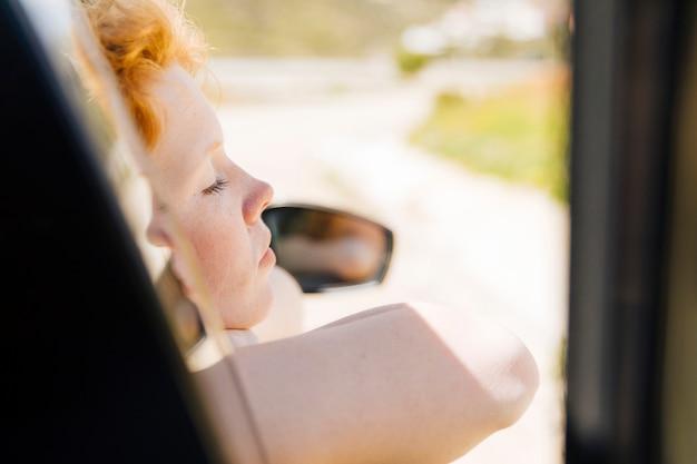 車の窓で眠っている女性