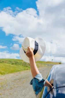 Рука женщины с шляпой против неба.