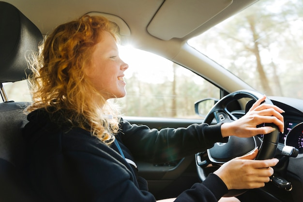 笑顔の赤毛の女性が車を運転