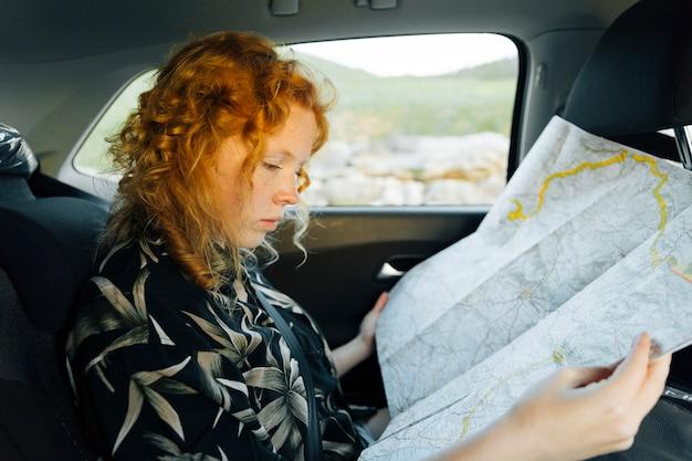 魅力的な若い女性は車に座りながら地図を見て