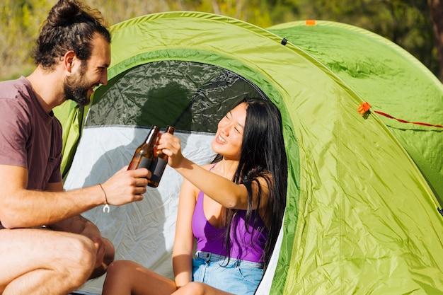 テントの中でリラックスした若いカップル