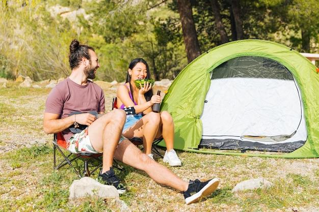 幸せなカップルが森でキャンプ