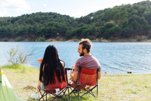 一緒に川岸に座っているカップル
