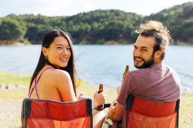 Молодая пара пьет пиво на берегу