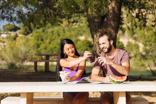 屋外のテーブルでビールを飲むカップル