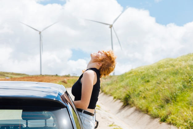 明るい日に車の窓から太陽を楽しむ女性