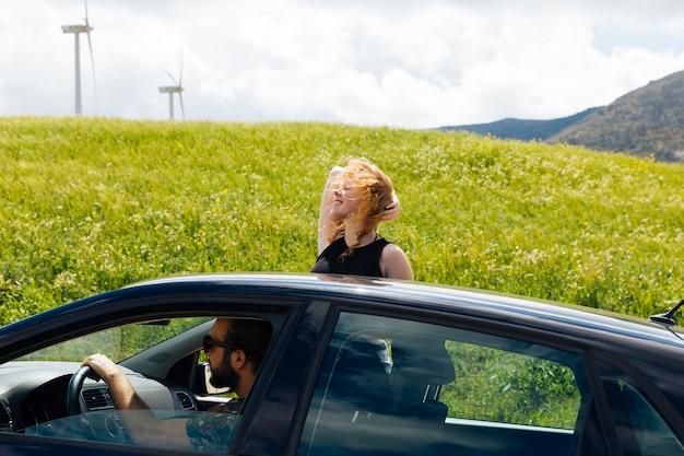 車の窓の外の道を見ている女性