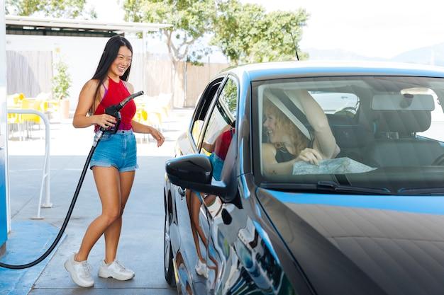 スリムなアジアの女性がガスノズルを押しながら車の中で友達に笑顔