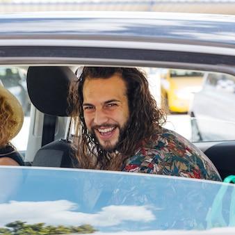 ガソリンスタンドで開いているウィンドウが付いている車に座っている男の笑みを浮かべてください。