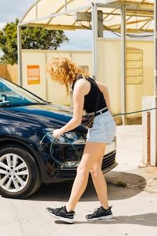 女性のガソリンスタンドで車のタイヤをポンピング