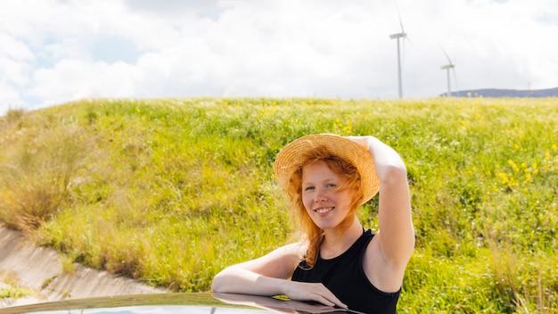 自然の中で赤い髪の巻き毛の女性の笑みを浮かべてください。