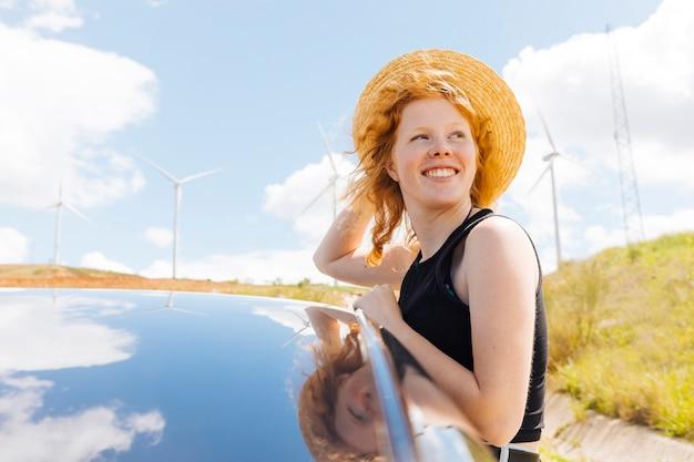 自然の中で風を楽しんでいる赤い髪の女