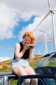 車の屋根の上のスイカを持つ女性