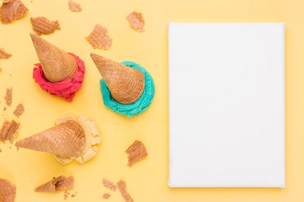 明るいフルーツアイスクリームひびの入ったワッフルと紙のシートをすくい取る
