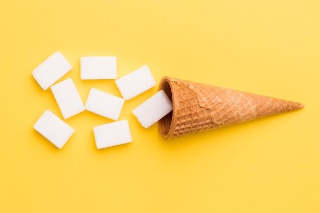 ワッフルコーンと黄色の背景に砂糖