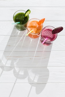 木製のテーブルの上のグラスにカラフルな飲み物