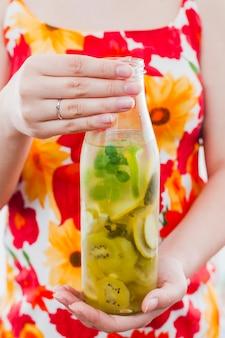 フルーツドリンクのボトルを保持している女性