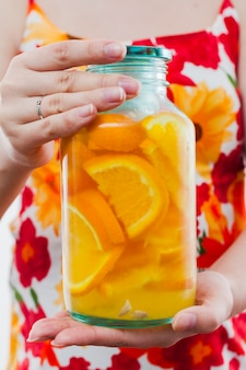 オレンジ色の飲み物の大きなボトルを保持している女性
