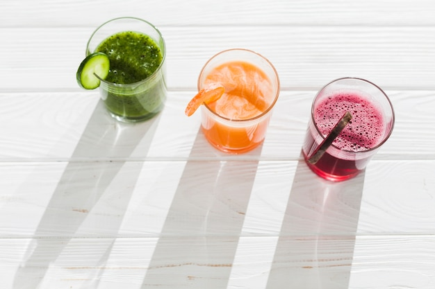 テーブルの上の色とりどりのスムージーのグラス