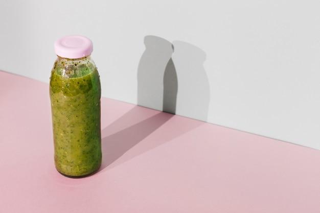 Бутылка зеленого смузи на столе