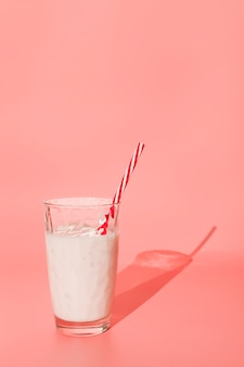 ピンクの背景にガラスのミルクセーキ