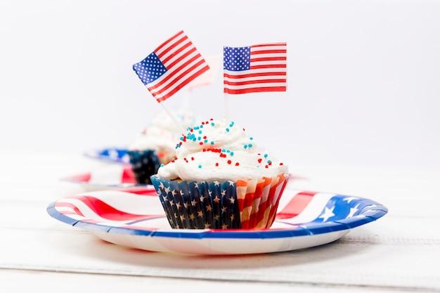 小さなアメリカ国旗と皿の上のトッピングケーキで飾られました