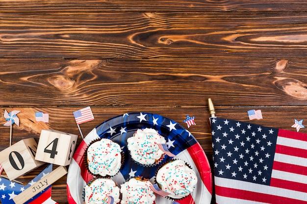 ホリデーケーキと独立記念日の間に木製のテーブルの上のアメリカの国旗