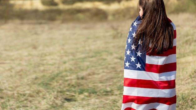 認識できない女性の独立記念日にアメリカ国旗を包む