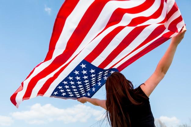 Женщина поднимает американский флаг в голубое небо.