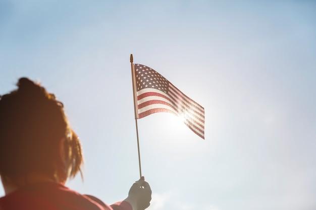明るい太陽にアメリカの国旗を上げる女性
