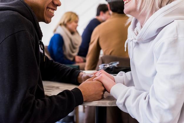 お互い手を取り合って異人種間の笑顔若いカップルのクローズアップ