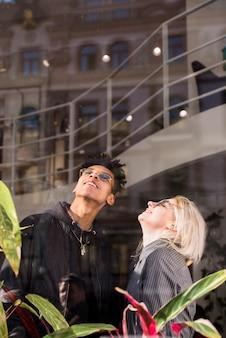 見上げるメガネをかけて魅力的な笑顔若いカップル