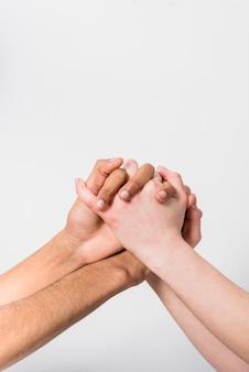 白い背景に対して互いの手を握って異人種間のカップルのクローズアップ