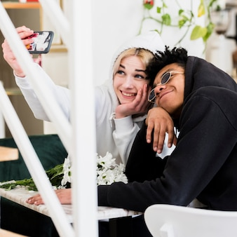 Милая счастливая межрасовая подростковая молодая пара, делающая селфи на мобильном телефоне