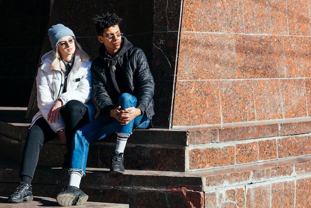 離れて見て階段に座っているファッショナブルな若い異人種間のカップル