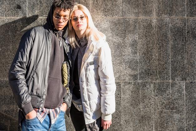 カメラ目線の灰色の壁に対してファッショナブルな若いカップルの立っています。