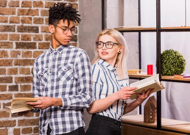 お互いを見て手で本を持って背中合わせに立っている異人種間の若いカップル