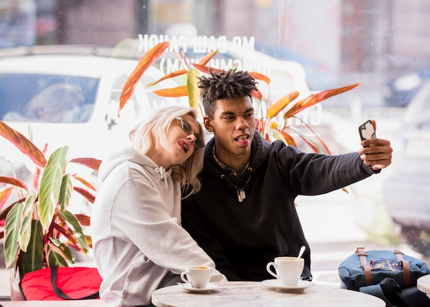 Межрасовые пары, сидя в кафе на открытом воздухе, принимая селфи на мобильный телефон