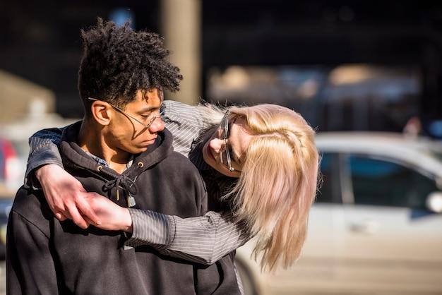 彼のアフリカのボーイフレンドを抱いて金髪の若い女性のクローズアップ