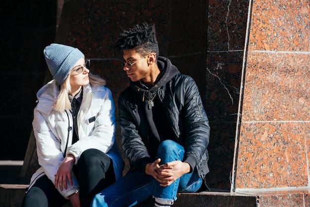 お互いを見て日光の下で座っている異人種間の若いカップル