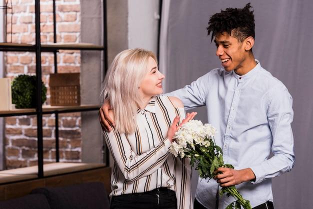 白い花の花束を与えることによって彼女のガールフレンドを提案しているアフリカの若い男