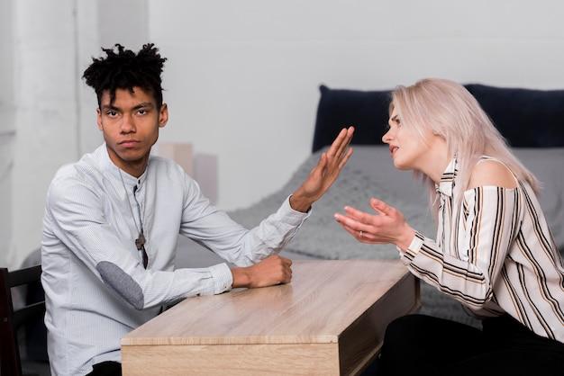彼と議論している彼女のガールフレンドを無視している若い男の肖像