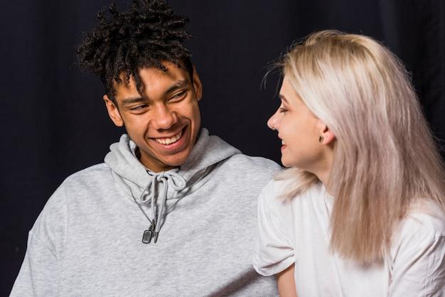 黒の背景に対して幸せな若いカップルの肖像画