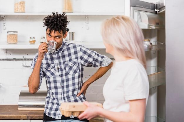 コーヒーを飲みながら彼女のボーイフレンドを見て手で卵のカートンを保持している若い女性